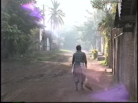 woman sweeps a dirt street in the morning light of posoltega, nicaragua. nicaragua is one of the poorest countries in the western hemisphere. - マナグア点の映像素材/bロール