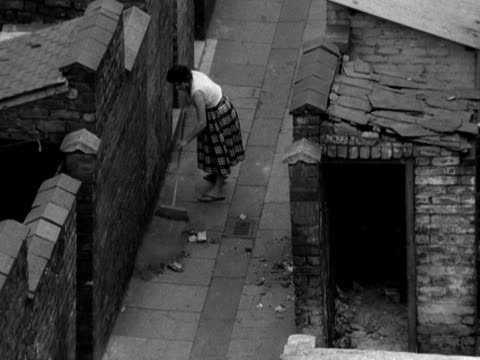 A woman sweeps an alleyway between slum houses in Salford