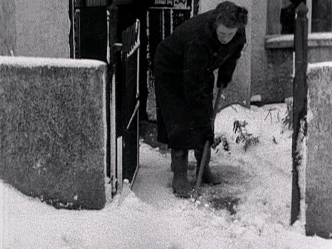 a woman sweeps snow from her path and picks up a milk bottle 1955 - milk bottle stock videos & royalty-free footage