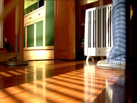 Woman sweeps wooden floor with mop