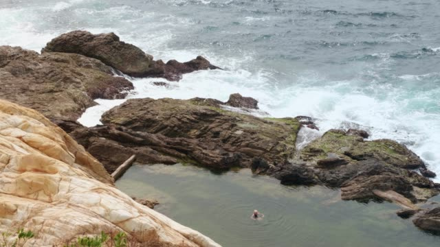 woman swimming and relaxing in tidal pool - leisure activity stock videos & royalty-free footage