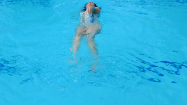 woman swimming backstroke in outdoor pool - backstroke stock videos & royalty-free footage