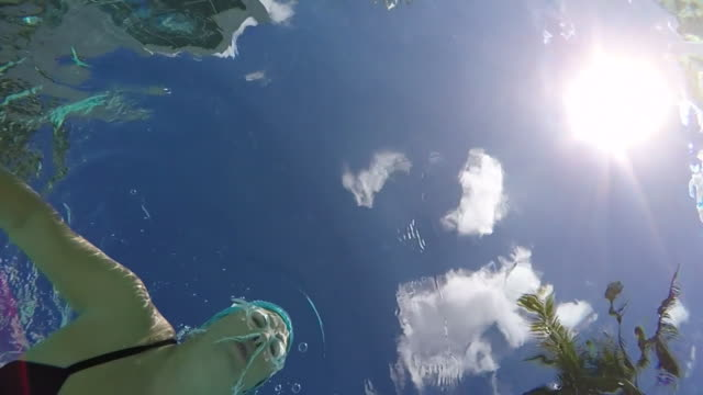 MS SLO MO Woman swimming breast stroke in pool, underwater shot taken from below looking up.