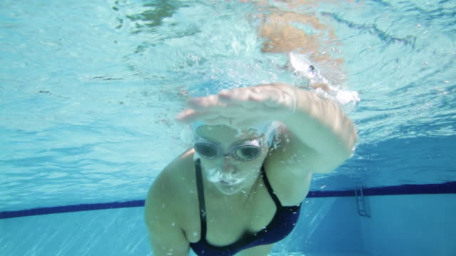 WS TS Woman swimming front crawl, front view underwater