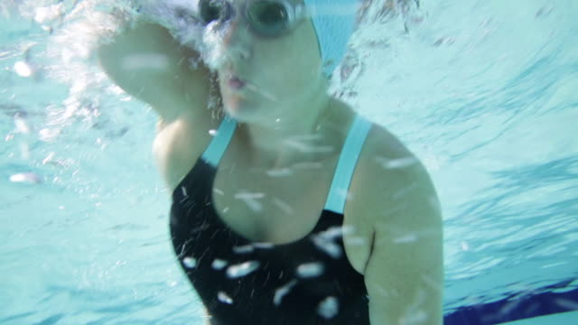 cu woman swimming front crawl underwater, front view. - swimming cap stock videos and b-roll footage
