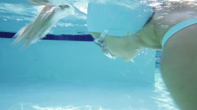 vídeos de stock, filmes e b-roll de cu woman swimming front crawl, underwater side view - touca de natação