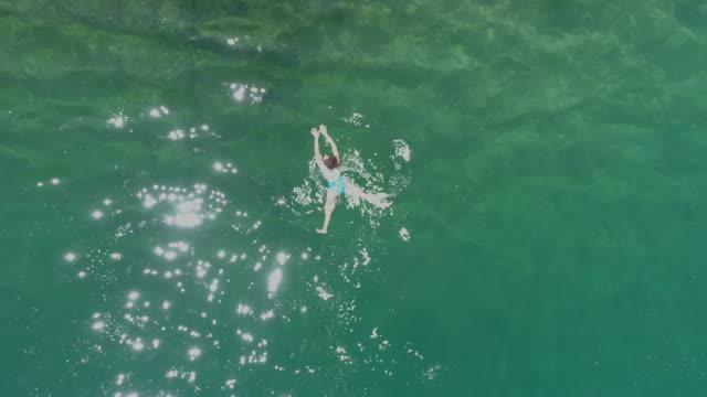 stockvideo's en b-roll-footage met vrouw zwemmen in het kristalheldere water - fatcamera