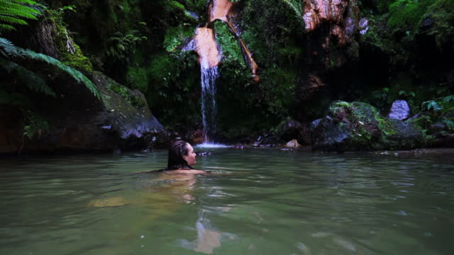 vidéos et rushes de woman swimming in natural hot spring with waterfall in the azores islands. - îles de l'atlantique