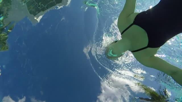 MS SLO MO Woman swimming in pool, underwater shot taken from below looking up.