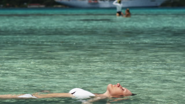 woman swimming in the ocean - isola di tahaa video stock e b–roll