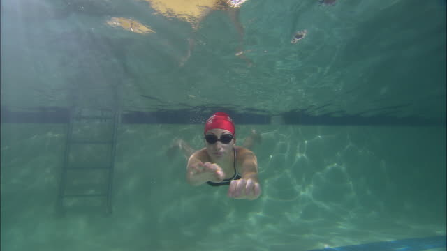 la ws woman swimming toward and above camera in pool and wearing swim cap and goggles / riverhead, new york, usa - swimming cap stock videos & royalty-free footage