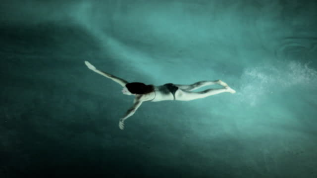 ws woman swimming under water at night / water mill, new york, usa - schwimmen stock-videos und b-roll-filmmaterial