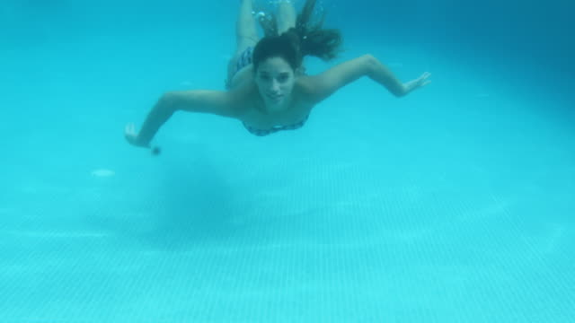 Woman swimming under water in pool