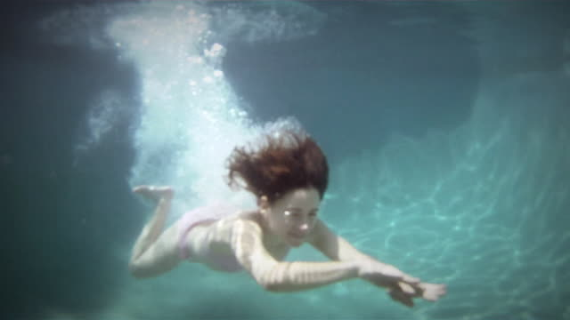 ms pan woman swimming under water in pool / water mill, new york, usa - 30 34 jahre stock-videos und b-roll-filmmaterial