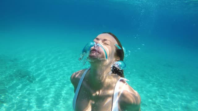 MS Woman swimming underwater in blue ocean