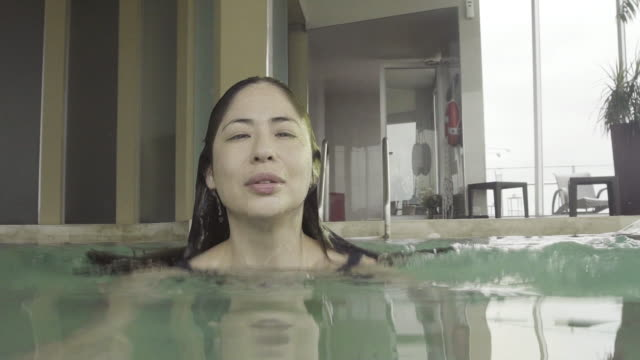 vidéos et rushes de woman swimming underwater in pool and then emerging to smile at camera - maillot une pièce