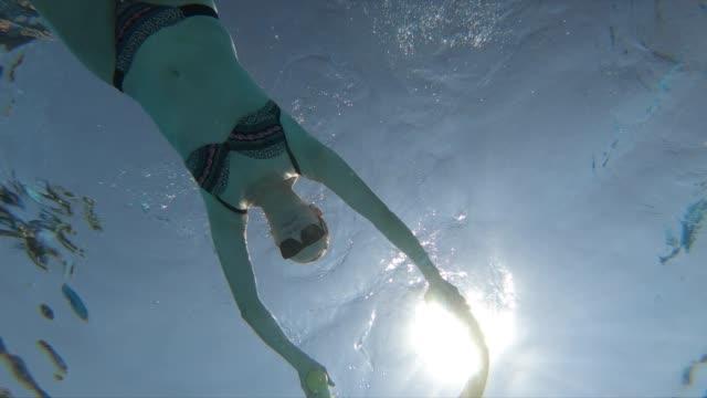 stockvideo's en b-roll-footage met vrouw zwemmen onderwater in resort zwembad - recht eronder