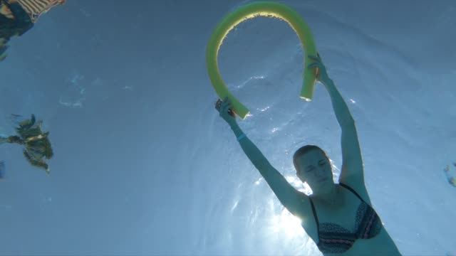 frau schwimmt unter wasser im resort-schwimmbad - schwimmen stock-videos und b-roll-filmmaterial
