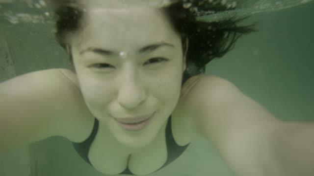 stockvideo's en b-roll-footage met woman swimming underwater - binnenbad