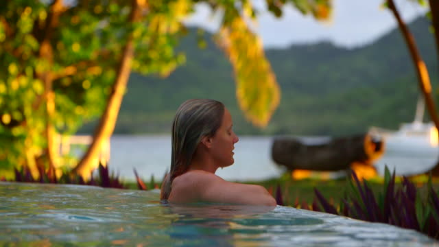 a woman swims in a hotel resort pool on a scenic tropical island in fiji. - fiji stock videos & royalty-free footage