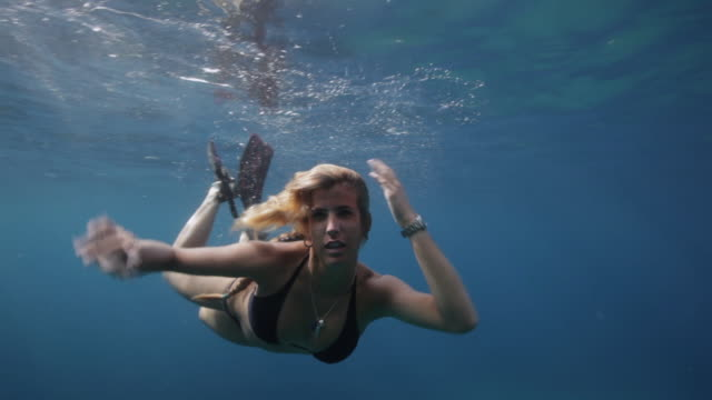 MS, SLO MO A woman swims underwater towards camera / Ibiza, Spain