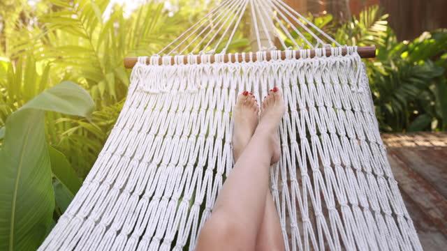 vídeos y material grabado en eventos de stock de mujer balancearse y relajarse en la hamaca - descalzo