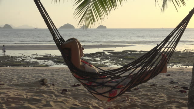 a woman swing in hammock on beach at sunset - woman hands behind head stock videos & royalty-free footage