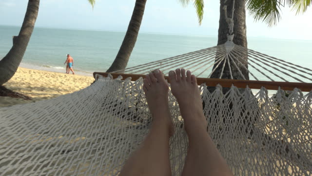 vidéos et rushes de pov / a woman swing in hammock on beach - hamac
