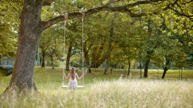 stockvideo's en b-roll-footage met slo mo ds vrouw swingen in het park - witte jurk