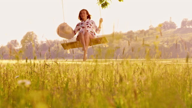 slo mo ds woman swinging on a beautiful sunny day - slovenia meadow stock videos & royalty-free footage
