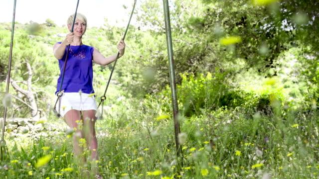 stockvideo's en b-roll-footage met ls ds woman swinging on a swing - jong van hart