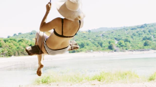 vídeos y material grabado en eventos de stock de slo mo mujer columpiándose en un columpio del árbol en la playa - hamaca