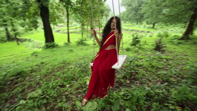 woman swinging on rope swing in a forest, malshej ghat, maharashtra, india - 揺れる点の映像素材/bロール