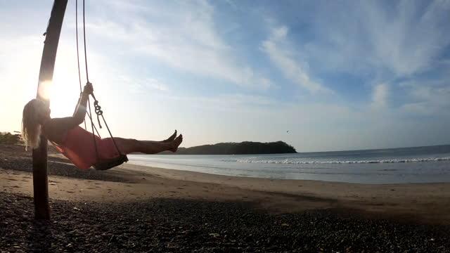 vídeos y material grabado en eventos de stock de mujer se balancea sobre la playa y surfea, en el asiento de madera - columpio