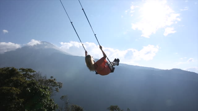 vidéos et rushes de woman swings high above valley below, towards sun - balançoire
