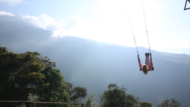 Woman swings high above valley below, towards sun