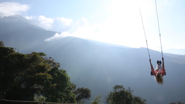 vídeos de stock e filmes b-roll de woman swings high above valley below, towards sun - baloiço