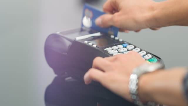 Woman swiping credit card and entering PIN code