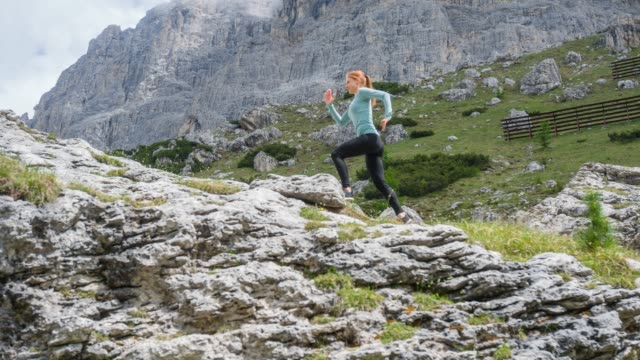 Woman tail running, leaving behind roads and tracks, and venturing onto dramatic mountain paths