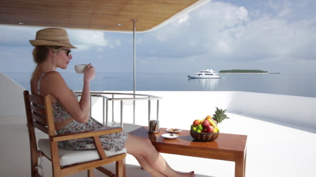 Woman take a breakfast on the deck of the yacht
