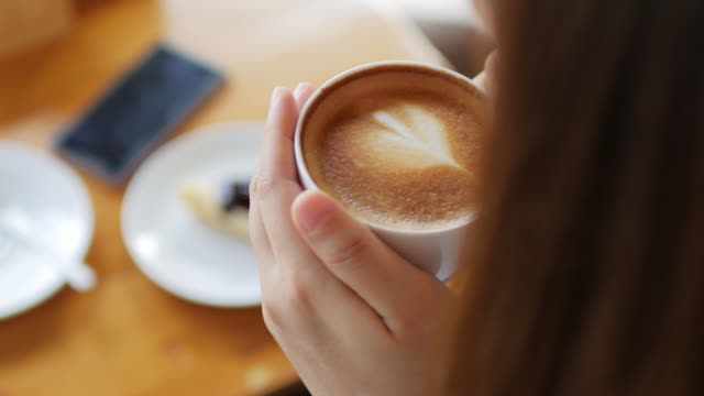 woman take a coffee latte art at coffee cafe , dolly shot left to right - coffee drink stock videos & royalty-free footage
