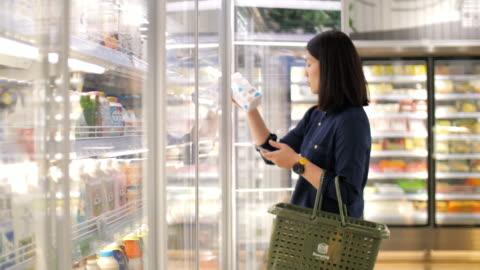woman take a fresh milk in supermarket , slow motion - shop stock videos & royalty-free footage