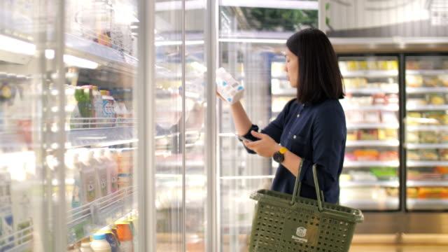 stockvideo's en b-roll-footage met vrouw nemen een verse melk in de supermarkt, slow-motion - supermarkt
