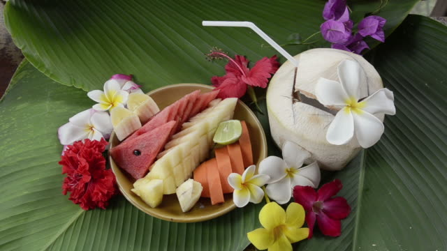 cu woman take banana from fruit salad and coconut drink decorated with frangipani flower / mae nam, ko samui, thailand    - fruit salad stock videos & royalty-free footage