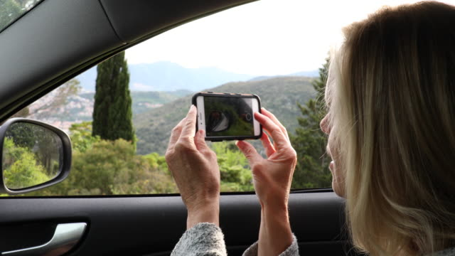 Woman take smart phone pic from car, hills below