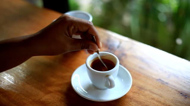 stockvideo's en b-roll-footage met vrouw nemen lepel en langskwamen koffie in een kopje koffie. - koffie drank