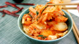 Woman take traditional korean cabbage appetizer Kimchi from bowl with chopsticks