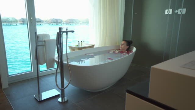a woman takes a bath in a bathtub bathroom view at a tropical island hotel resort. - bath stock videos & royalty-free footage