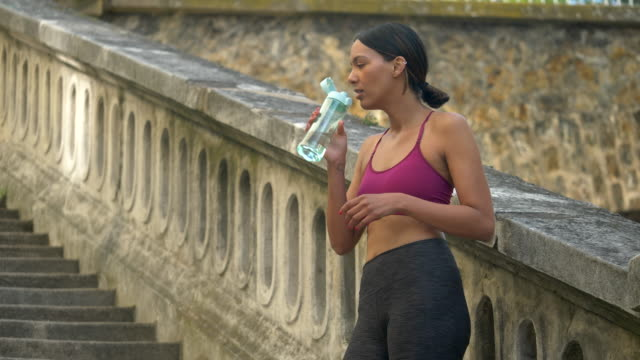 a woman takes a break after a workout to drink water. - slow motion - flasche stock-videos und b-roll-filmmaterial