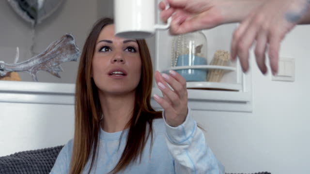 Woman takes a cup of coffee while working at home